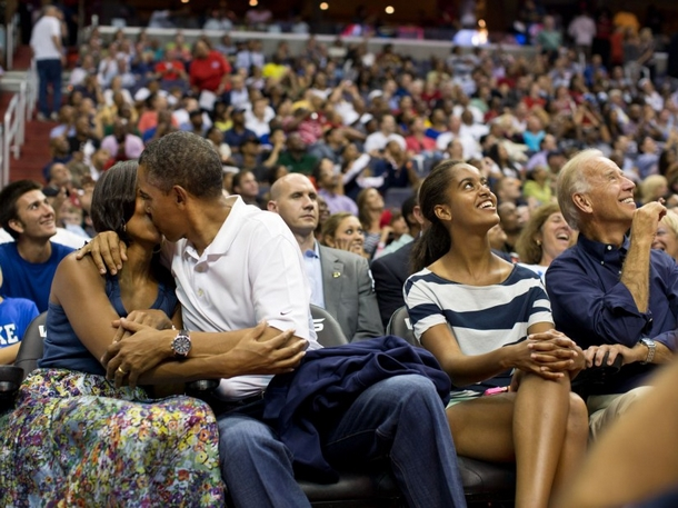 Barack et Michelle Obama s'embrassent sous l'œil de la caméra lors d'un match de basket-ball opposant la sélection américaine et l'équipe du Brésil, le 16 juillet 2012, à.jpg